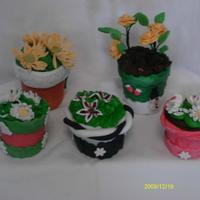 Candy Flower Pots these are candy flower pots. the pot is made of fondant and the flowers of gum paste.Inside of the flower is melted candy melts. and the...