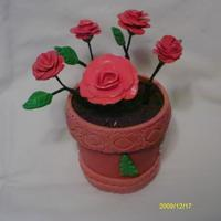 Red Roses flower of gum paste base of pot made of fondant and oreo dirt and inside of pot chocolate candy.