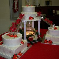 Poinsettia Wedding Cake  For a December wedding, the poinsettias on the cake are piped on, but the ones on the stairs are artificial. It has snowflakes stamped on...
