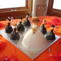 Bridal Shower  Bride with 6 bridesmaid cakes, all done in buttercream. There were orange and fushia crisscrosses on the back of each dress. The bride has...