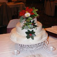 Christmas Wishes 2 tier Christmas Cake, the topper is made from gumpaste. it contains. pointsetta, american holly, english holly, pine cones, pine, spruce,...