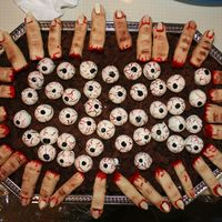 Fingers And Eyeballs Fingers made from NFSC with red piping gel for blood. Eyeballs are cake truffles dipped in white chocolate and painted with food coloring...