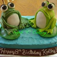 Rrrrribbit!!! 9x13 base cake iced with IMBC. Frogs are made in the mini wondermold pan, iced wth IMBC and covered with fondant. Frogs copied after ones...