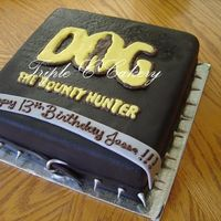 "Dog The Bountyhunter 10"" chocolate cake iced with IMBC, covered with chocolate fondant and airbrushed black with a chocolate transfer for the logo. Dog..."