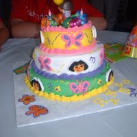 Dora The Explorer   3 tiered - buttercream icing - dora themed with butterfly napkins, plates, and cups. Combined the two different themes on the cake.