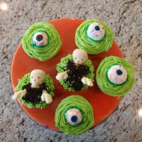Spooky Cupcakes Orange creamsicle cupcakes, buttercream iced, eyeballs are fondant painted with Amerigels, Skulls are candy molds