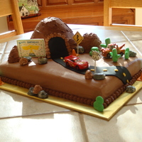 Cars Birthday Cake  Yellow cake with chocolate buttercream frosting; marshmallow fondant rocks, construction cones, cacti; gumpaste signs; fondant road. Thanks...