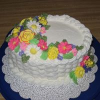 Course Ii Final Cake White buttercream icing over two layer oval yellow cake.
