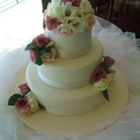 Wedding Cake Three tier, ivory fondant and fresh flowers.