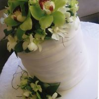 Wedding Cake This is a three tier cake with fondant in a draped look. It has fresh flowers.