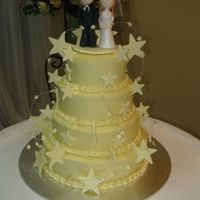 Wedding Cake Four tier mud cake covered with white ganache and white chocolate stars, topped with sugar bride and groom.