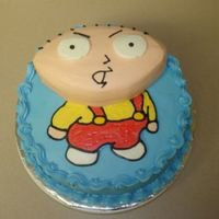 "Stewie Cake 10"" white cake filled with whipped cream and strawberries, iced in buttercream. The head is just carved cake, also iced in buttercream..."