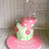 Wonky Birthday Cake 2 tier vanilla sponge wonky cake. Gerberas and swirls around the bottom tier, random flowers over top. topper with beading, board done with...