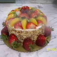 Any Ocassion Fruit Cake Yellow with whip topping icing & garnished with toasted almonds, fresh peaches, grapes, kiwii, and strawberries
