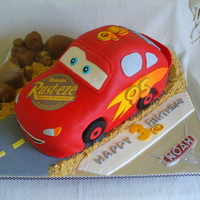 Cars Lightning Mcqueen First car (kindof) cake. Not as easy as I'd hoped! All fondant decorations, cookie crumb sand, fondant covered cookie wheels, finished...