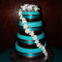 Wedding Cake Covered in chocolate and teal fondant with gumpaste flowers. Yellow cake with strawberry mousse, fresh strawberries and covered in...