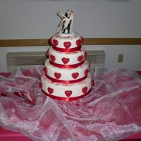 Red Hearts Wedding Cake 4 tier, Vanilla/Chocolate Fudge Marble cake, whipped chocolate hazelnut BC filling, covered in vanilla BC, and fondant. Hearts are Wilton...