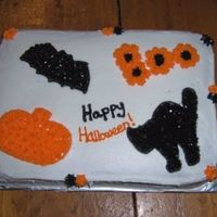 Happy Halloween Orange (yellow) cake with buttercream frosting and decorations.