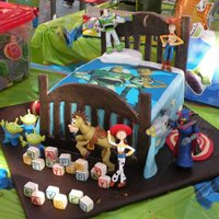 Toy Story Bedroom Cake Edible.. Bed frame and bed, floor, blocks, rug, ball are all Fondant... Edible cake image on bedspread. Toy figurines.