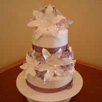Mauve Lilly Wedding Cake This cake was a 15cm and 20cm caramel mud cake covered in caramel frosting and fondant icing. The lilies and filler flowers were made from...