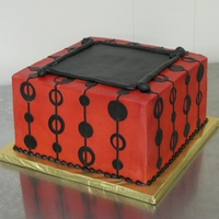 "Red And Black 9"" square iced in buttercream with fondant accents."