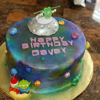 "Buzz Lightyear Cake This was for my 4 year old nephew who adores Buzz Lightyear. It is a 10"" WASCWC frosted with Sugarshacks buttercream. I airbrushed the..."