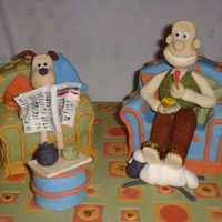 Wallace And Gromit I made this as a raffle prize for the school fair. The armchairs are madiera cake covered in fondant, and the rest is just fondant!