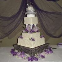 3 Different Pattern Square Wedding Cake Each tier has a different design. Used silk flowers around base and between pillars.