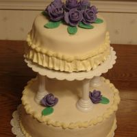Wilton Cake Course Iii This is a two tiered cake. Each are two layers cakes filled with buttercream icing. Ivory colored fondant was placed over each cake. The...