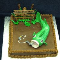 The One That Got Away! fishing cake for a 70 year old man. cake is buttercream. fish is rice krispie covered in fondant, sign is gumpaste with edible marker...