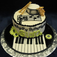 Music Teacher's Cake 9 inch chocolate cake with carmel filling. fondant sax, piano, and drum and sticks. very fun to make. The saxophone almost drove me crzy,