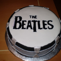 Beatles Drum Bass drum with Beatles logo on it. Fondant covered chocolate cake. Logo created by stencil and painting food coloring.