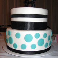 "Retro Wedding Cake   White fondant iced, turquoise dots, black ribbon and a retro looking ""B"" top it off."