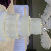 """bling"" Cake White fondant icing, pearlized harlequins, silver dragees, HUGE fake diamond and feathers on top."