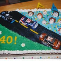 Birthday Cake For Nascar Fan faces and flags made from fondant, cars were foil covered chocalate i bought.