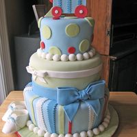 Train Baby Shower  This cake was designed to match the baby's bedding. Covered in MMF, bows and baby shoes made from 50/50 fondant/gumpaste. Thanks for...