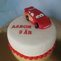 Lightning Mcqueen Vanilla sponge cake filled with strawberry mousse and raspberry mousse. Covered in sugar paste.I made McQueen in modeling paste.