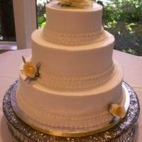 Brandywine I 3 tier buttercream with hand piped lace and yellow silk roses.