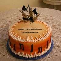 "Jonathon 10"" round iced in buttercream and airbrush orange. Music notes and insturments are made from fondant."