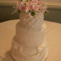 Brandywine Ii 3 tier fondant with drapes, cornelli lace, quilting w/ perals and gumpaste flowers.