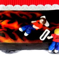 Skateboard Cake   Two gumpaste figures atop chocolate mint cake w/bc frosting. Airbrushed flame details gumpaste wheels. TFL