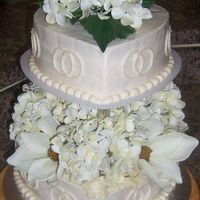 Ivory Heart-Shaped Wedding Cake This is a wedding cake for a couple that wanted a heart shaped cake with entwined rings incorporated in the cake. The flowers used on the...