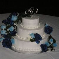 Blue Rose Cake 3 tier vanilla bean cake, raspberry cream filling, and chocolate with banana filling. Blue silk roses cascade at customer request.