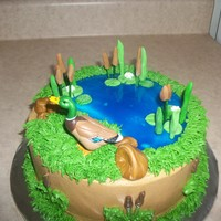 Duck Hunter Cake Purchased duck cake with buttercream icing, blue piping gel for water, lily pads and cattail made out of fondant.