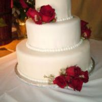 White Fondant With Red Roses Simple yet elegant wedding cake with bead border.