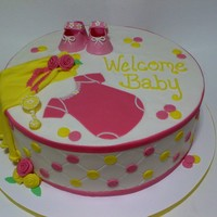 Pink And Yellow Baby Shower 12 Inch cake Buttercream with fondant details. The booties were 50/50 gumpaste and fondant. My first time doing the diamond pattern, and by...