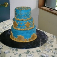 Blue Buttercream With Gold Fondant This is a gingerbread cake with lemon buttercream for a High School event.