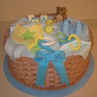 Baby Shower Basket Cake Cake iced and decorated in chocolate buttercream with fondant/gumpaste decorations on top.