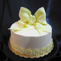 Gum Paste Daisies Buttercream Cake This cake is just plain swiss buttercream with a fondant bow and gumpaste flowers.