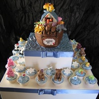 Noahs Ark - Christening Cake Lots of fondant animals sitting on a white mud cake covered in dark ganache and then covered in fondant. There are 36 cupcakes :) The...